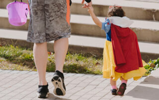 Trick-or-treating toddler princess with dad