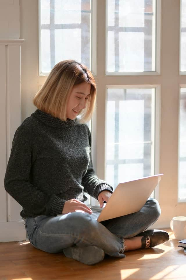 young woman sitting on floor and typing on laptop